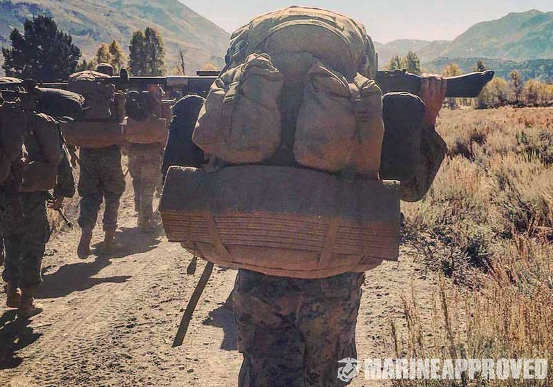 Marine Carrying a Heavy Backpack with a Sleeping Pad Attached